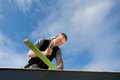 Roofer hammering a nail into roof beam against bright blue sky Stock Photography