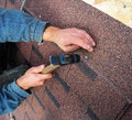 Roofer installs bitumen roof shingles - closeup on hands. Roofin Royalty Free Stock Photo