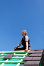 Roofer sitting on top of a roof an unfinished sunny day Royalty Free Stock Photo