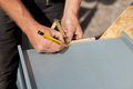 Roofer using a pencil and ruler to make markings folding on metal sheet Stock Photography