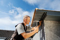 Roofer working on a new dormer by hammering nails into the roof edge Royalty Free Stock Photo
