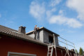 Roofer working on a new dormer roof standing the rooftop Stock Photography