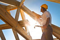 Roofer working on roof structure sunflare Stock Photography