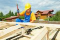 Roofer works on roof carpenter worker nailing wood board with hammer installation work Stock Photos