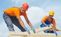 Roofers carpenters works on roof two construction roofer carpenter worker installing wood board Royalty Free Stock Photo