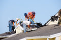 Roofing construction crew tearing old shingles off of the roof of a building to prepare the surface for putting on new shingles Royalty Free Stock Photo