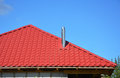 Roofing Construction. New red metal tiled roof with steel chimney house roofing construction exterior without rain gutter system. Royalty Free Stock Photo