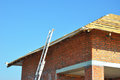 Roofing Construction. Roof-trusses. Wooden Roof Frame Unfinished House Construction with metal ladder. Royalty Free Stock Photo