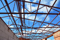 Roofing construction. Steel roof trusses details with clouds sky background.