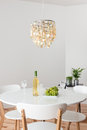 Room with decorative chandelier and white round table plants Stock Photo