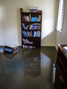 Room with flood water waters in a a bookcase books in the this was a result ing the storm surge floods in sandgate in Royalty Free Stock Images