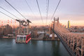 Roosevelt island tramway at sunset with cable car between manhattan and with koch bridge in midtown Stock Photo