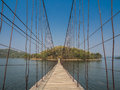 Rope bridge direct to lonely island across the lake in Stock Photography