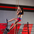 Rope climb exercise woman workout at gym climbing Royalty Free Stock Images