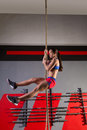 Rope climb exercise woman workout at gym climbing Stock Image