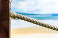 Rope fence on wooden pillar, sea and beach in background. Royalty Free Stock Photo