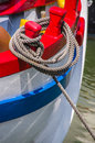 Rope mooring hawser attached to brightly coloured red stanchions on the stern of a boat in harbour Royalty Free Stock Images