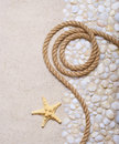 Rope and starfish on pebbles sea Royalty Free Stock Photo