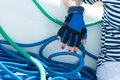 Rope woman in vest her hand in a blue glove near the blue wire Stock Image
