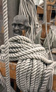 Ropes around a wooden cleat head shaped on an old vessel Stock Images