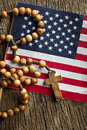 Rosary beads with american flag top view of on wooden background Royalty Free Stock Photo