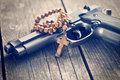 Rosary beads and gun Royalty Free Stock Photo