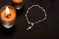 Rosary beads with an orange candle in black background, above view Royalty Free Stock Photo