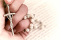 Rosary on book hand holding white above blured Royalty Free Stock Image