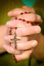 Rosary in hands holding red with cross Stock Photography