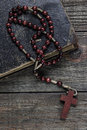 Rosary and old book on wooden table Royalty Free Stock Image