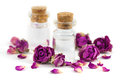 Rose aroma oil two fragrance bottles filled with with purple dried buds and petals isolated on white background Royalty Free Stock Photography