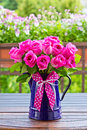 Rose bouquet enamel jug bow of pink roses in a blue with a of pink ribbon outdoors copy space Royalty Free Stock Photo