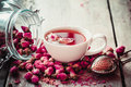Rose buds tea, tea cup, strainer and glass jar with rosebuds Royalty Free Stock Photo