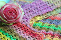 Rose on colourful background pink made of layers of multicoloured crochet garments Royalty Free Stock Images