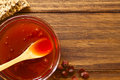 Rose hip jam homemade in glass bowl with wooden spoon photographed overhead on wood with natural light selective focus focus on Royalty Free Stock Image