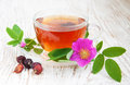 Rose hip tea cup of on a wooden background Royalty Free Stock Photos