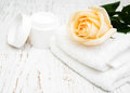 Rose with moisturiser cream and towels on a wooden background Royalty Free Stock Photography