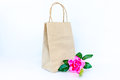 Rose pink flower with paper shopping bag isolated on the white b Royalty Free Stock Photo