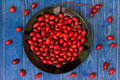 Rosehip on blue wooden table Royalty Free Stock Photos