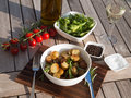 Rosemary roasted potatoes with vegetables dinner served on a wooden plate Stock Images