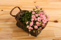 Roses in a basket bunch of small pink over wooden table Royalty Free Stock Images