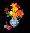 Roses on black background colorful in blue and white decorated jug Stock Photography