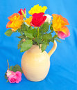 Roses on blue jug of background with a pink rose beside the beige colored vase Stock Photography