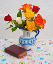 Roses and book of common prayer decorated blue white vase with colorful beside it antique Royalty Free Stock Image