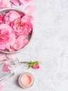 Roses in gray bowl with water cream and pink bottle with booth on stone background Stock Images