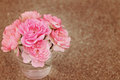 Roses in vase on brown sweet pink a clear glass with sandy background with shallow depth of field and a beautiful retro filter Royalty Free Stock Photography