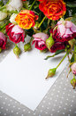 Roses and white cardboard on a gray fabric Royalty Free Stock Photo