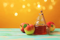 Rosh hashanah jewish new year holiday celebration concept. Honey and apples over yellow background Royalty Free Stock Photo