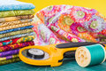 Rotary cutter and spool of thread on a background fabric Royalty Free Stock Photos