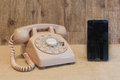 Rotary phone and smart phone cream with a black Royalty Free Stock Photo